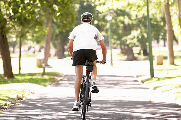 Rear View Of Mature Man Cycling Through Park Away From Camera During Camera